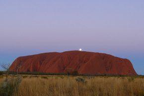 Die Sonne ist gerade untergegangen, als sich der Vollmond über dem Uluru zeigt.